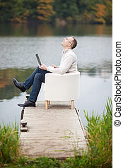 Happy Mature Man Using Laptop While Sitting At Pier - Full...