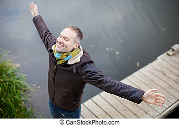 Man With Arms Outstretched Standing On Pier - High angle...