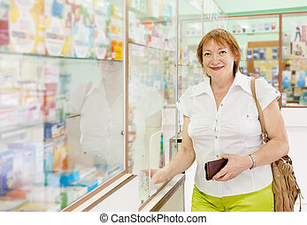 woman buys drugs at pharmacy - Mature woman buys drugs at...