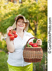 woman with basket of harvested vegetables - Happy mature...