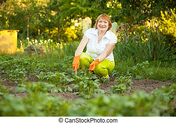 mature woman working in field - Happy mature woman working...