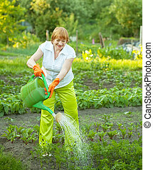 woman watering with watering pot - Mature woman watering...