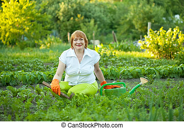 Happy mature woman working in garden - Happy mature woman...