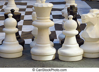 Big Chess - Very large white Chess Pieces in front of Black...