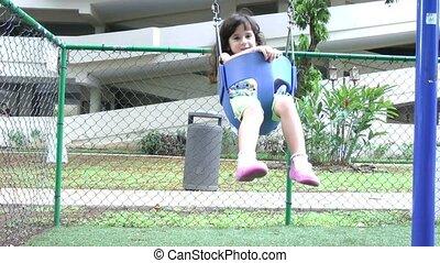 slow motion, a little girl swings