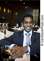 Indian Business Man Sitting In Restaurant With a Drink