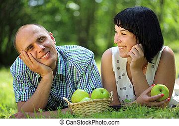 Young couple with apples lying on grass