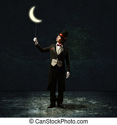 magician keeps the moon on a string - magician in top hat...