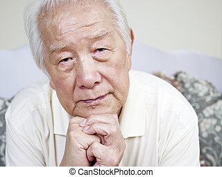 asian senior man - portrait of a sad asian senior man.