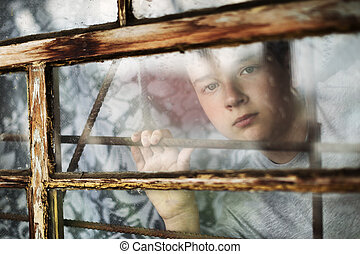 The boy looks out of the window through a lattice - The boy...