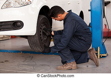 Rotating tires at an auto shop - Young mechanic rotating...