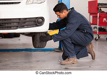 Changing a tire at an auto shop - Young handsome mechanic...