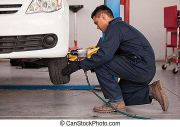 Tightening bolts of a tire - Young mechanic using an air gun...