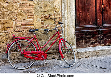Red bicycle leaning against a wall in Pienza