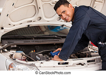 Changing oil of a car - Happy young mechanic pouring some...