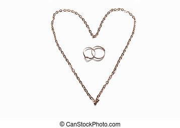 Heart laid out from a gold chain and wedding rings.