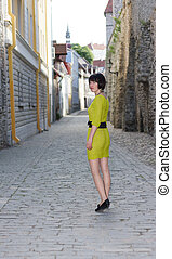 Woman in yellowish dress walks on a street - Young woman in...