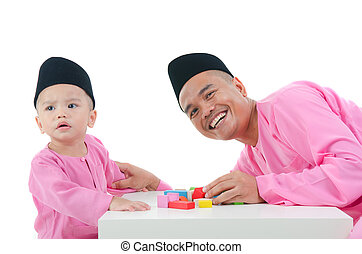 happy malay father and son, in traditional baju melayu...