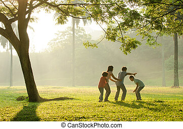 an asian family having fun playing in the park early morning