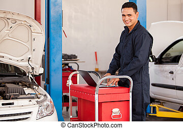 Using a computer at an auto shop - Happy young mechanic...