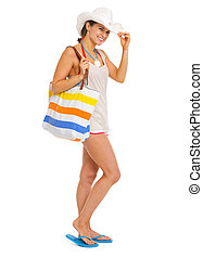 Full length portrait of happy young woman with beach bag