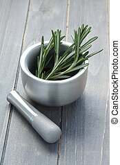 Metal mortar and pestle with rosemary on wooden background