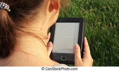 girl reading an e-book in nature in summer day
