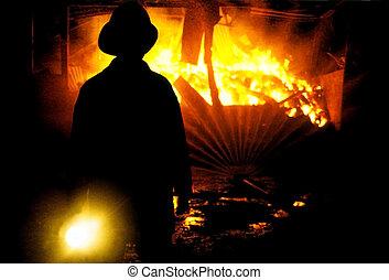 Fireman shing torch - Rear view of fireman shining torch on...