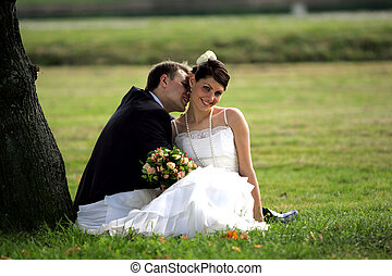 Newlywed couple kissing in summer under shade of tree.