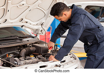 Using jumper cables to start a car - Young handsome mechanic...