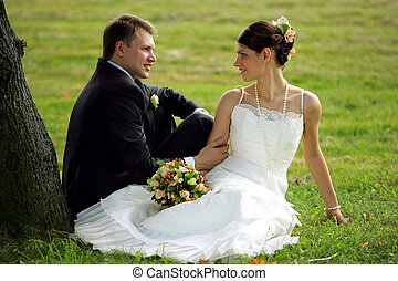 Newlywed couple in love - Newlywed couple sat in field under...