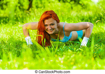 Young girl doing press ups on the grass