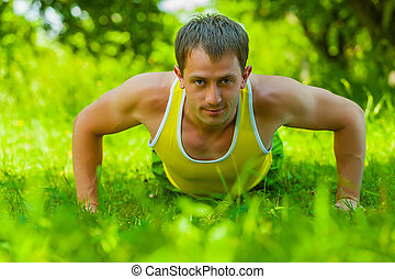 Young man doing press ups on the grass