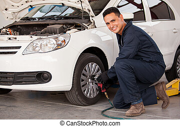 Rotating tires at an auto shop - Handsome young man using an...