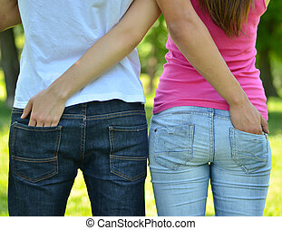Teenagers couple outdoor with hands in each others pockets