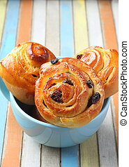 Fresh sweet swirl buns with raisins on colored wooden table