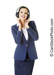 Happy attractive businesswoman listening the music through...