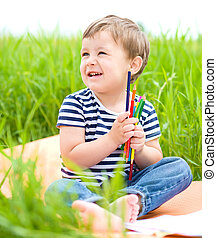 Little boy is playing with pencils