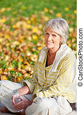 Senior Woman With Water Bottle In Park