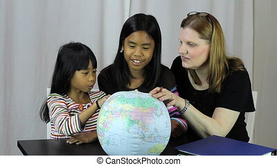 Homeschool Teacher Uses Globe - A pretty housewife uses a...