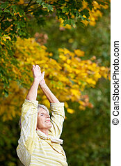 Senior Woman Doing Stretching Exercise In Park - Senior...