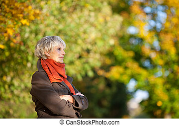 Senior Woman Arms Crossed Looking Away In Park - Thoughtful...