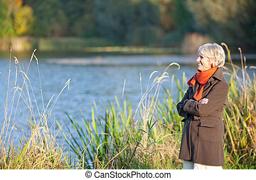 Senior Woman Enjoying Sunlight At Lake - Happy senior woman...