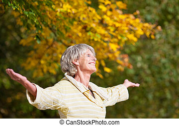Senior Woman Enjoying Nature In Park - Senior woman with...
