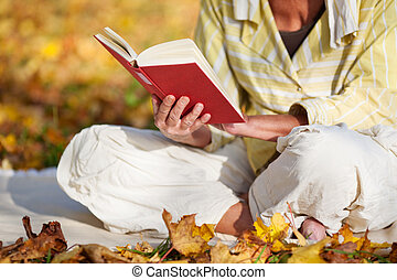 Reading Book In Park - closeup of senior woman reading book...