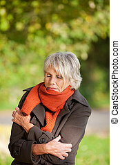 Senior Woman Shivering In Park - Senior woman with eyes...
