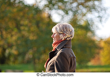 Senior Woman In Park - Side view of senior woman in jacket...