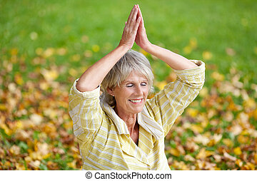 Senior Woman With Hands Clasped Meditating In Park