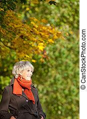 Senior Woman In Jacket Looking Away In Park - Happy senior...