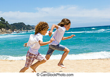 Two boys running on beach - Two boys having a race on sunny...